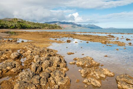 rocky beach near Plum on eastern coast of New Caledonia at low tide Stock Photo