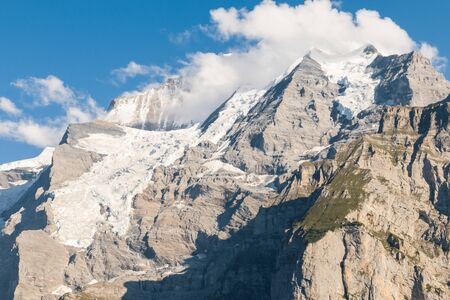 Eiger glacier covered by cumulus clouds in Bernese Alps, Switzerland