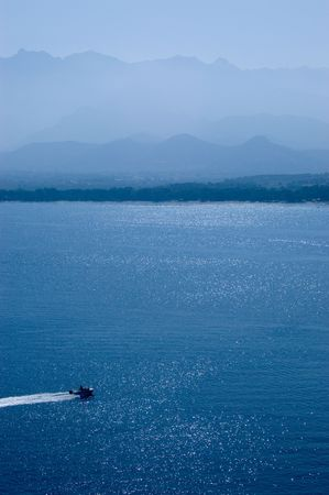 High speed motorboat on sunshined sea with mountains on horizont