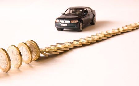 Queue of euro coins falls, red german car