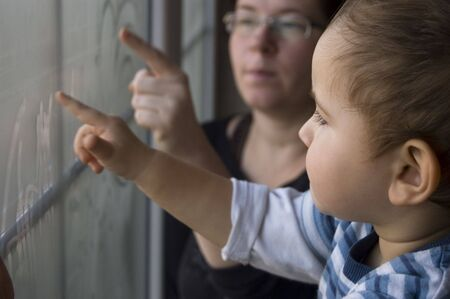 Mom and two years old son paint on window  Stock Photo