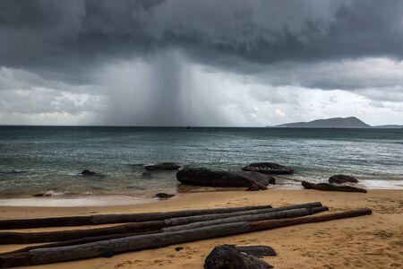 strong rain cloud beach and trunks on island koh rong cambodia Reklamní fotografie