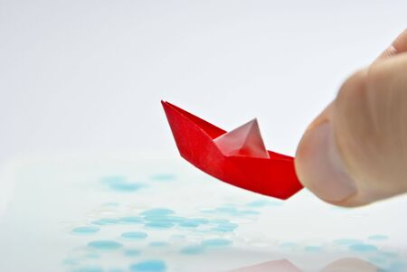 leasure: Red Origami Sail Boat floating in water