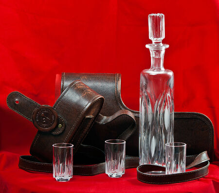 decanter: Leather case for a crystal decanter and glasses on red background Stock Photo