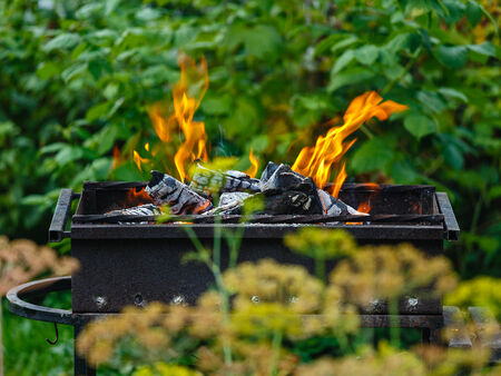 Burning coals in a brazier in the middle of a green garden