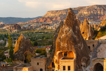 Hotel rooms cut down in the rock in the light of the setting sun. Cappadocia, Turkey