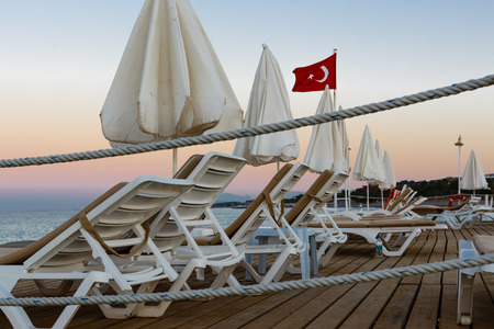 lounges: Chaise lounges and sun-protection umbrellas on a wooden pier in Turkish resort on a beach of Mediterranean Sea