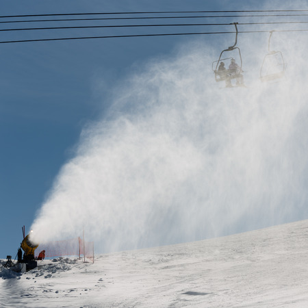 Snowmaking spraying snow on the piste for mountain skiers photo