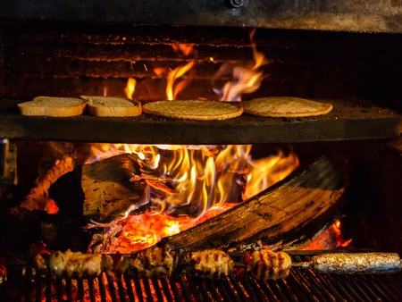 woodfire: Bread and flat cakes roasted on fire in a fireplace at small Bulgarian restaurant Stock Photo