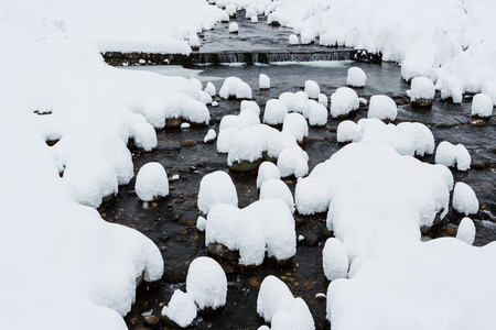 wintery snowy: Snow caps on boulders in the mountain river formed after heavy snowfall