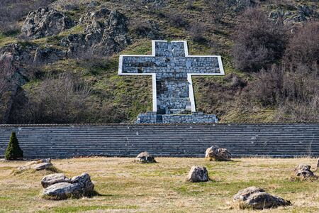 Christian cross laid out of stones on the slope of the mountain