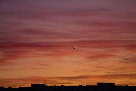 Silhouettes of homes and plane on background of sunset in freezing weather