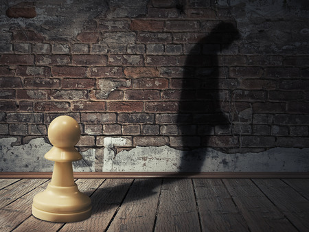 demotion: A white pawn piece into a dark room with its man silhouette shadow on a brick wall