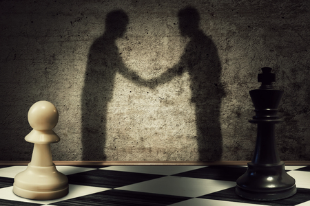business leadership: Chess pawn and king standing in front one another with their shadow transform into businessman giving handshake. Business hierarchy peace Stock Photo