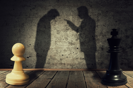 failed strategy: Chess pawn and king standing in front one another with their shadow transform into businessman silhouettes. Business hierarchy misunderstanding