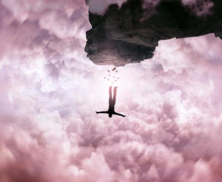 산의 피크에서 점프하는 젊은 남자의 실루엣, 하늘 배경에 절벽. 자유와 위험 개념.