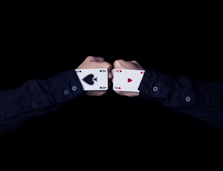 swindler: Two fists colide. A pounch of two aces on a black background