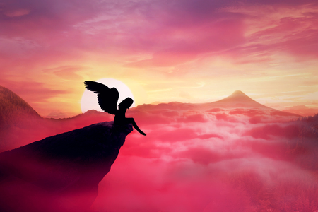 Silhouette of a lonely fallen angel with long wings standing on a cliff against a paradise sunset. Dusk sky over the clouds in the mountains. Heaven landscape scene screen saver Standard-Bild