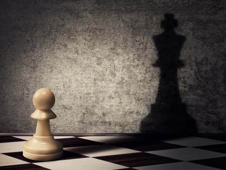 mind games: pawn chess piece casting a shadow of a king on a concrete wall. Business aspirations and leadership concept. Magical transformation
