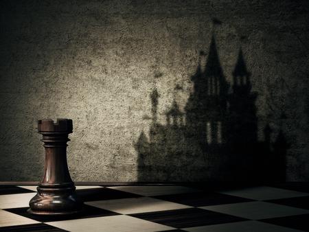 castillo medieval: Torre pieza de ajedrez que echa una sombra en forma de un castillo en un muro de hormigón. aspiraciones empresariales. transformación mágica
