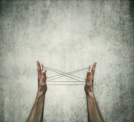 Two human hands playing cats cradle game with a thread on a grey concrete background. Creative thinking concept