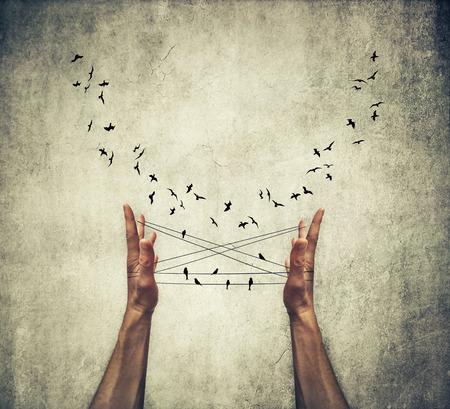 男の手はワイヤ上のように立って、周りを飛んで、鳥と猫クレードルをゲームのスレッドに関連付けられています。鳥を誘導ましょう。いくつかの 写真素材