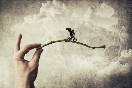 taking a risk: Boy riding a bicycle try to jump over a chasm. Self overcoming and risk taking concept Stock Photo