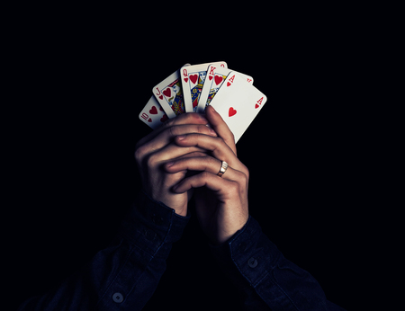strongest: man hands holding playing cards with the strongest combination - royal flush Stock Photo