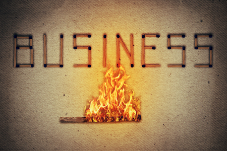 burned out: Burning match setting fire to its neighbors in arranged in shape of business word. Ignited match stick  as a symbol for business risks and dangers.