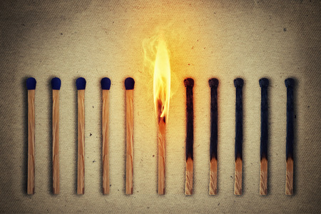 sequential: Burning match standing middle a row of whole, new matches at left and extinguished at right. Leadership concept
