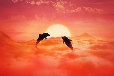 夕日の背景に雲の上にジャンプ 2 つの遊び心のあるイルカのシルエット。シュールな野生生物の風景シーン スクリーン セーバー 写真素材