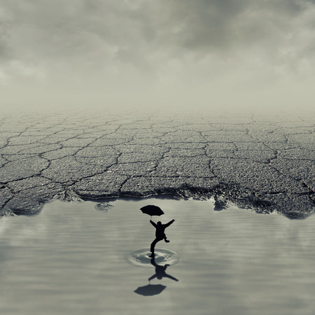 Surrealistic image with a boy jumping in a pothole of cracked asphalt. Broken pavement with a dirty water puddle. Stock Photo