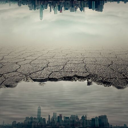 Surrealistic image with a city reflect in a pothole of cracked asphalt. Broken pavement with a dirty water puddle.