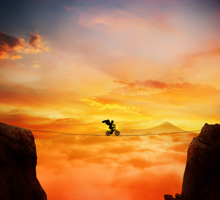 risk taking: Boy with angel wings balance on a rope over a chasm riding a bicycle.Self overcoming and risk taking concept. Beautiful sunset background over the clouds