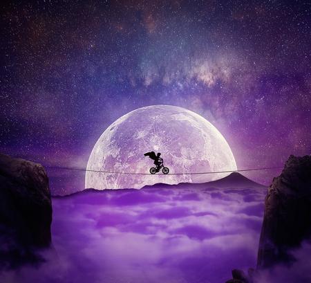 天使と少年は、自転車に乗って割れ目にワイヤーでバランスを翼します。自己克服とリスク概念。雲の上の満月の夜背景