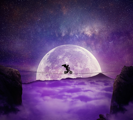 noche y luna: Muchacho con las alas del ángel equilibrio sobre un alambre sobre un abismo que monta una bicicleta. Auto superación y la asunción de riesgos concepto. Antecedentes completos noche de luna sobre las nubes Foto de archivo