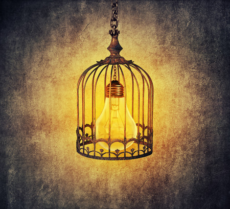 locked in: Light bulb locked in a old cage. Locked idea concept Stock Photo