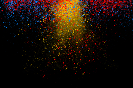 Freeze motion of colorful powder coming down isolated on dark black background. Abstract design of falling yellow, blue and red dust. Particles cloud wallpaper.