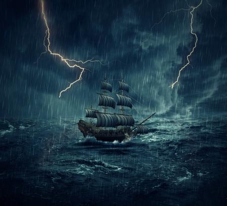 Vintage stary żaglowiec stracił w oceanie w deszczowej, burzliwej nocy z piorunów na niebie. Przygoda i podróż koncepcja