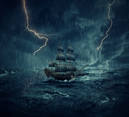 Vintage, old sailing ship lost in the ocean in a rainy, stormy night with lightnings in the sky. Adventure and journey concept Archivio Fotografico