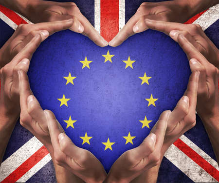 european community: Human hands make heart shape with patterned flag of the European Community inside and the flag of the United Kingdom outside