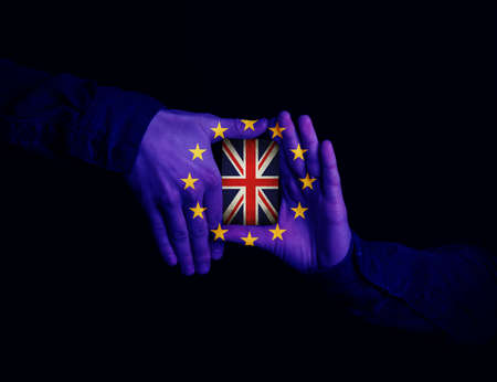european integration: Close up of hands patterned with the flag of the European Community holding a card with the flag of the United Kingdom. Magician showing his trick with cards on black background