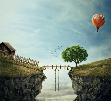 2 つの丘を結ぶ木橋と国のイメージ。フェンスと崖と途中でスイングの近くの木と古い小屋ののどかな景色 写真素材