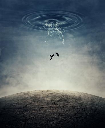 ひびの入った砂漠の地面にダウン クラッシュ水のしぶきとして空から落ちて傘を持った若い男のシルエット。ビジネス リスク、失敗、損失の概念