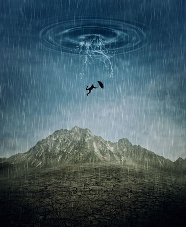 A silhouette of an young man with an umbrella falling from the rainy sky as a splash of water crashing down to the cracked desert ground. Business risk, fail and loss concept