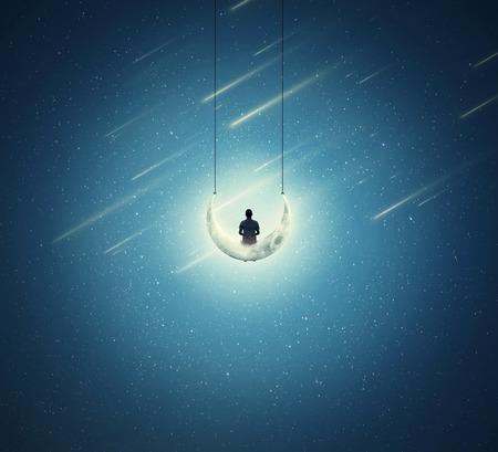 星空の上、スイングとして、三日月の上に座って孤独な少年と超現実的な背景