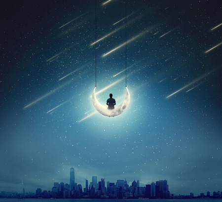 Surreal background with a boy sitting on a crescent moon, as a swing, over a big city in a starry night
