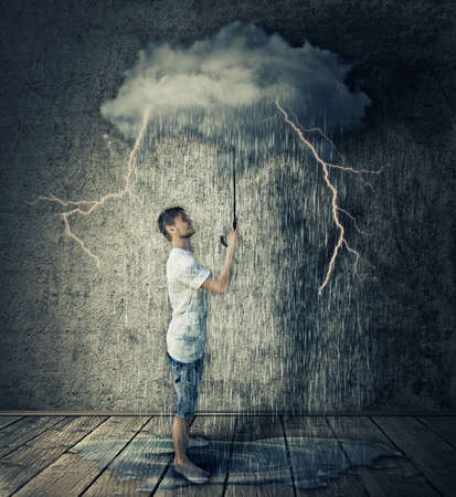 pessimism: Happy boy stand in a room, holding a stormy, rainy cloud as umbrella. Business pessimism concept
