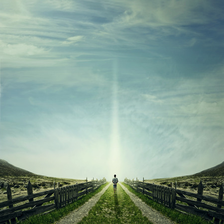 Man walking on a country road with a relax mood, following a light. Way of life concept Stockfoto