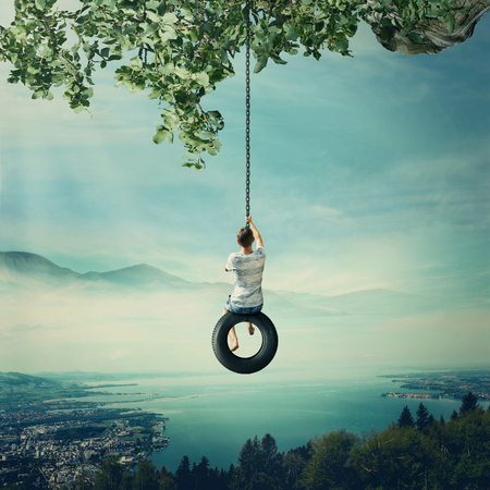 Young boy swinging on a tire over the foggy city with lake and forest background. Having fun and freedom concept Foto de archivo